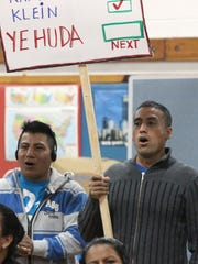 Luis Nivelo of Spring Valley, right, holds a sign during