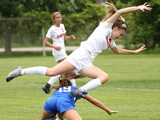 Flying over Salem's Maddy Servey (19) is Canton freshman