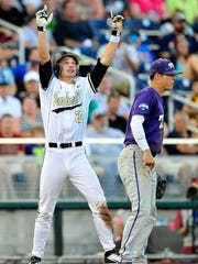 Vanderbilt's Bryan Reynolds, left, reacts next to TCU's Derek Odell after hitting a triple during the fifth inning in the College World Series at TD Ameritrade Park, Friday, June 19, 2015, in Omaha, Neb.