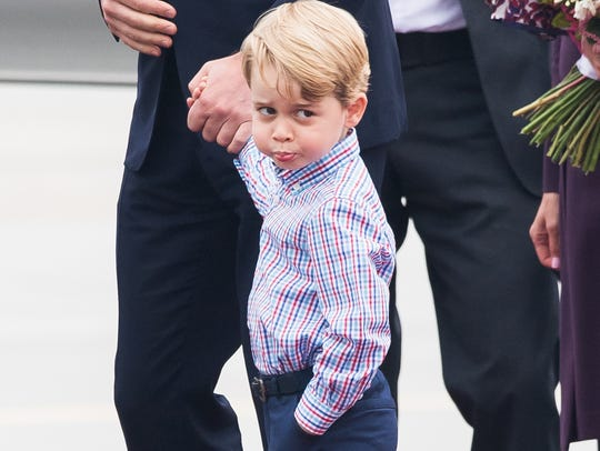 Prince George aims a scowl towards the media at the