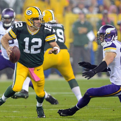Green Bay Packers quarterback Aaron Rodgers (12) dodges