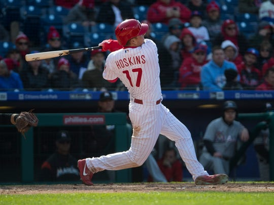 Phillies' Rhys Hoskins (17) swings at a pitch during the Phillies home opener against the Miami Marlins at Citizens Bank Park.