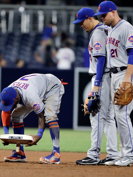 New York Mets shortstop Jose Reyes, left, takes second base as teammates first baseman Lucas Duda (21) and third baseman Wilmer Flores, second from right, look on after defeating the San Diego Padres in a baseball game Monday, July 24, 2017, in San Diego. Reyes stole the 500th base of his career during the game. (AP Photo/Gregory Bull)