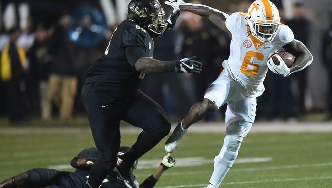 Tennessee running back Alvin Kamara (6) escapes from Vanderbilt defensive lineman Adam Butler (69) during the first half at Vanderbilt Stadium on Saturday, Nov. 26, 2016.