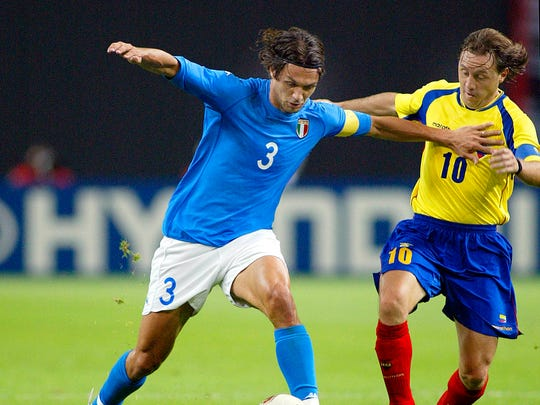 Italian team captain Paolo Maldini, left, holds of the challenge of Ecuador's captain Alex Aguinaga during the 2002 World Cup Group G soccer match.