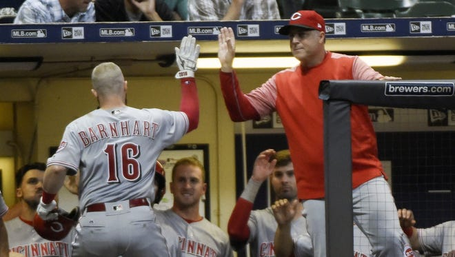 Reds manager Bryan Price congratulates catcher Tucker Barnhart after his seventh-inning home run in Friday's game in Milwaukee.