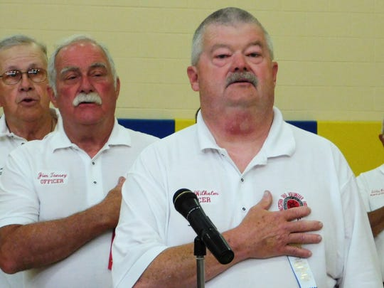 Put-in-Bay Assistant Fire Chief Mark Wilhelm, front, here reciting the Pledge of Allegiance at the recent firefighters' convention in Green Springs, said staffing was a frequent topic of conversation.