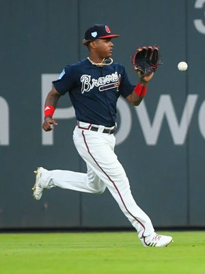 Atlanta Braves' Cristian Pache fields a line drive by Cincinnati Reds' Matt Kemp who singled during the seventh inning of an exhibition baseball game on Monday, March 25, 2019, in Atlanta. (AP Photo/John Amis)