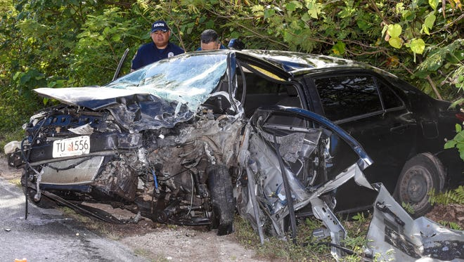 Guam Police Department officers conduct an traffic investigation of a crash involving this black Toyota Yaris and a white Mitsubishi Outlander on Route 15 in Yigo on Wednesday, June 14, 2017.
