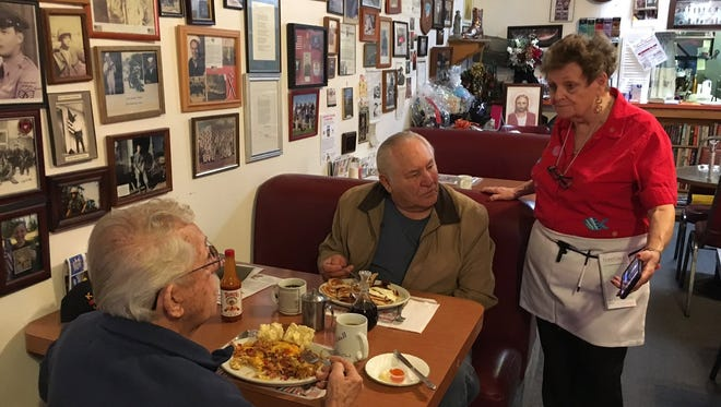 Klassique Kafe co-owner Millie Ellis shares an inauguration ceremony broadcast on her cellphone with two customers Friday.