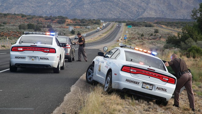 Utah Highway Patrol troopers question the occupants of a grey Nissan Sentra that was reported stolen after pulling the vehicle over on Interstate 15 near mile marlker 24 Tuesday, Oct. 6, 2015.