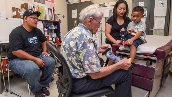 Pediatric Orthopedic Surgeon, Dr. Robert Nemechek, front, looks over an ankle and foot orthotic device belonging to patient Elijah Castro, 4, during a visit to a Shriners Hospital For Children-Hawaii outreach at the Department of Public Health and Social Services in Mangilao on Thursday, July 20, 2017. Parents, Annalyn and Joshua Castro, say that the free medical services provided by the Shriners Hospital has been a tremendous help in treated their son who was experiencing difficulty in walking.