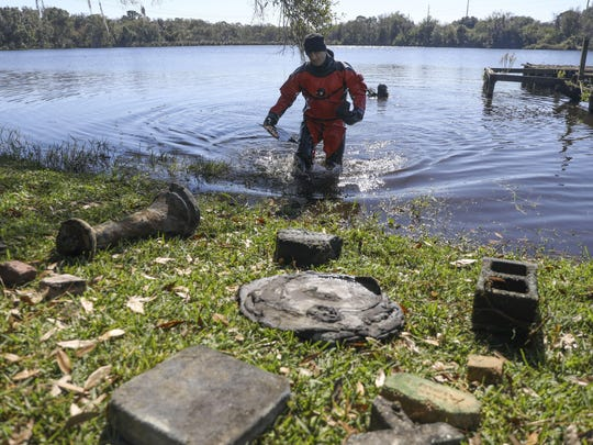 Hillsborough County Sheriff's deputy Alton Smith walks from a lake with items that theyre recovered Jan. 22 at Bay Tree Farm in Odessa, Fla., amid the search for Keystone Memorial Cemetery.