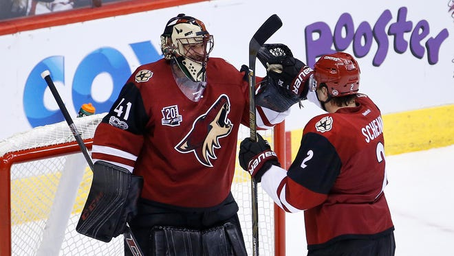 Coyotes' Mike Smith (41) celebrates with defenseman Luke Schenn (2) after a 3-0 shutout against the Canucks at Gila River Arena on January 26, 2017 in Glendale, Ariz.