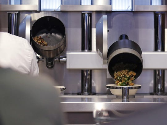 Customers wait as their automatically prepared food