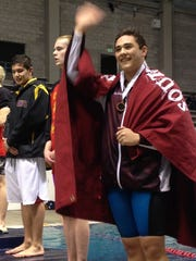 South Kitsap's Dylan Macabitas waves to the crowd after receiving his fourth-place medal in the 100-yard backstroke Feb/ 20, 2016 at the Class 4A state boys swimming and diving championships.