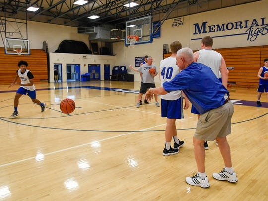 Memorial basketball coach Rick Wilgus passes the ball as he runs the Tigers through drills at Thursday's practice.