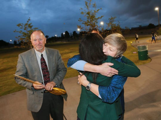 Elaine Williamson, right, embraces city Rep. Claudia Ordaz at the conclusion of a ribbon-cutting ceremony Thursday for John Lyons Park, which honors Williamson's late husband. City Parks and Recreation Director Tracy Novak is at left.