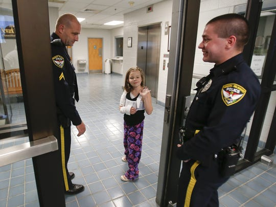 Newark Police Cpl. Andrew Pagnotti, left, and Officer Dan Burgess accompany Emily Ruckle as she visits the department on the way home from the hospital.