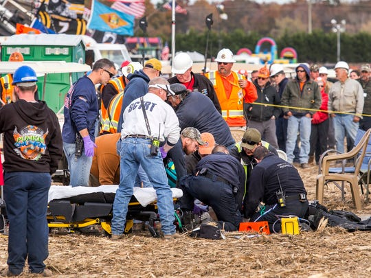 Paramedics tend to an injured person after a piece of metal flew off of an air cannon at the World Championship Punkin Chunkin.