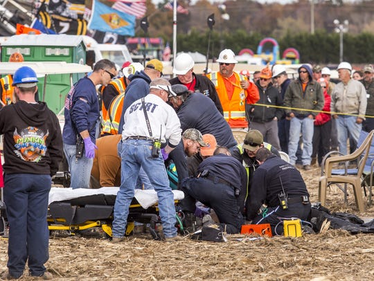 In this file photo, paramedics tend to an injured person after a piece of metal flew off of an air cannon, striking them in the head, at the World Championship Punkin Chunkin in Bridgeville.