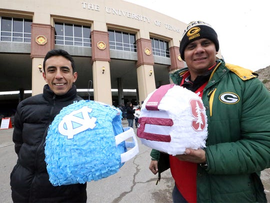 Israel Contreras, left, and Eric Terrones hold opposing team piñatas Friday outside Sun Bowl Stadium.