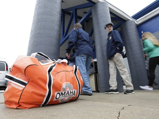 People shuffle past an equipment bag from an Omaha,