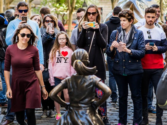 "Tourists gather to take photos of the ""Fearless Girl"" and ""Charging Bull"" statues in New York City on Sunday morning, April 23, 2017."