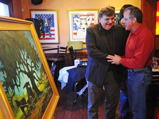 "George Rodrigue, left, talks with David Begnaud, one of many supporters on hand for the unveiling of Rodrique's latest painting the ""Youngsville Heritage Oak,"" Tuesday, Feb. 8, 2011, at the Blue Dog Cafe in Lafayette."
