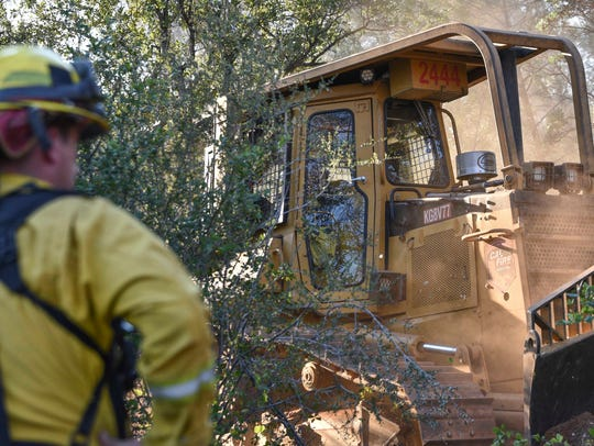 A firefighter watches as a bulldozer breaks free from