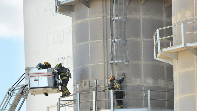 Firefighters make their way back to an aerial ladder truck while inspecting an elevator after an explosion at the Central Valley Ag Cooperative grain elevator in Hinton on Thursday. The explosion shook the entire town, according to witnesses.