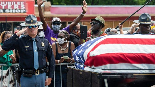 "Alabama State Troopers salute the coffin of civil rights icon and U.S. Congressman John Lewis at the spot where he was beaten by the same force during the 1965 ""Bloody Sunday"" Selma-to-Montgomery march on the Edmund Pettus Bridge in Selma, Ala., on Saturday, July 26, 2020."