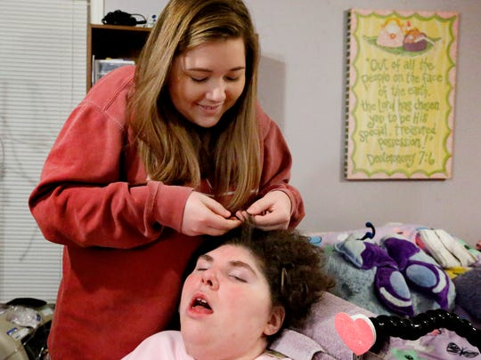 "Anna Roan, 16, braids her sister Alison ""Ally"" Roan's hair. Ally was born with Spastic Quadriplegic Cerebral Palsy and has been under around the clock nursing care most of her life. When Roan recently turned 21 TennCare dropped her care from 24/7 to just 30 hours a week. Roan's family is fighting to keep her at home and not moved to a nursing care facility."