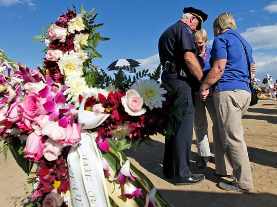 "Aurora Deputy Police Chief Terry Jones, left, prays with Ginger Sanders, from Gadsden, Ala., and Toni New, from Kingsport, Tenn., at the memorial across from the movie theater, Wednesday, July 25, 2012 in Aurora, Colo. Twelve people were killed and over 50 wounded in a shooting attack early Friday at the packed theater during a showing of the Batman movie, ""The Dark Knight Rises."" (AP Photo/Alex Brandon)"