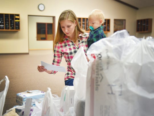 Michaela Hofer and her son Micaiah sort through check