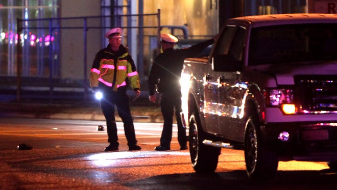 Police investigate the scene of a fatal accident in Fairfax Monday night. A woman was struck and killed crossing Red Bank Road.
