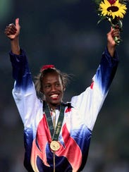 Jackie Joyner-Kersee gives a thumbs up on the medals
