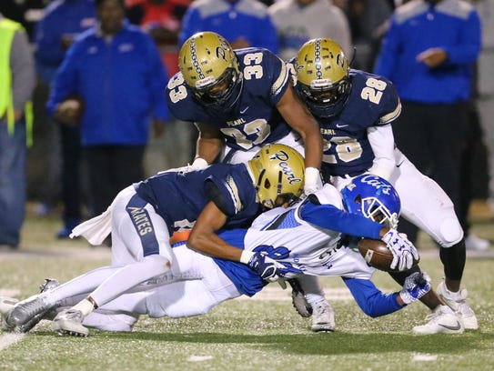 Meridian's John Spinks (87) reaches for extra yards
