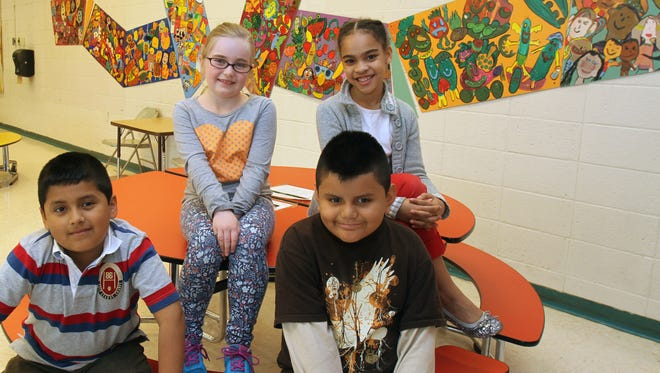 From left, Highview School third graders Sergio Collana, Niamh Spillane, Alexis Paute and Taylor Hendrickson are photographed in the school cafeteria near the nutrition-based mural that they helped to create May 9, 2014.