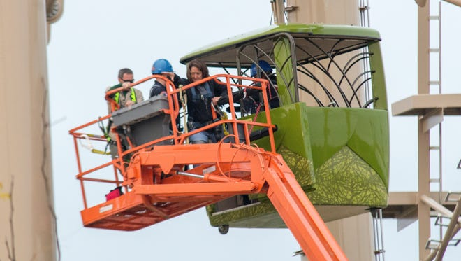 Donna Wininger, Plainfield, steps from a motionless sky car onto a lift used to rescue her and five others trapped 35 feet in the air at the Indianapolis Zoo on Sunday, Oct. 12, 2014. Twelve other riders were stuck on a lower level.
