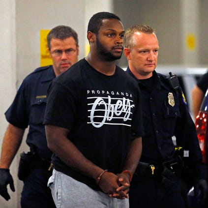 Phoenix police officers escort Arizona Cardinals running back Jonathan Dwyer, 25, to the 4th Avenue Jail following his arrest on suspicion of aggravated assault.