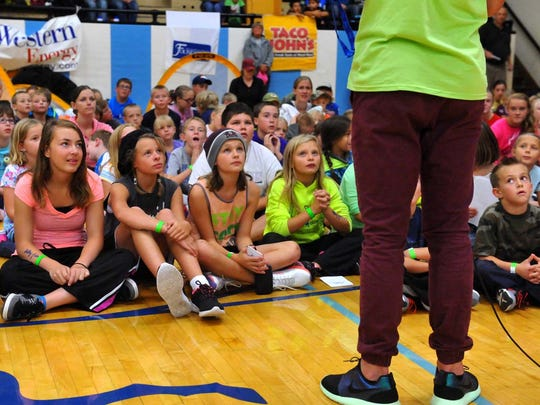 Kids listen intently as Abby Wamback talks about the improtance of exercise and nutrition during Get Fit Great Falls' fourth annual Come Out and Play event at Great Falls High School, Saturday, September 5, 2015.
