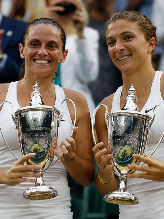 Roberta Vinci of Italy, left, and Sara Errani of Italy hold their trophies after defeating Timea Babos of Hungary and Kristina Mladenovic of France in the women's doubles final at the All England Lawn Tennis Championships at Wimbledon, London, Saturday July 5, 2014.  (AP Photo/Sang Tan)