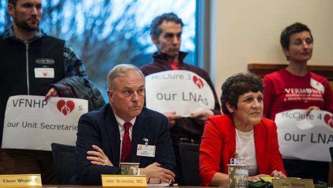 Dr. John Brumsted, left, and Allie Stickney of the University of Vermont Medical Center's board of trustees, listen as supporters of the hospital's licensed nursing assistants having their own union speak during a meeting of the trustees in Burlington on Thursday, December 8, 2016.