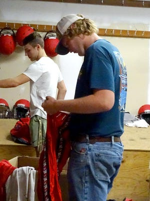 Ottawa High School junior football players Reese Fogle and Adam Doran select their uniforms and other football gear as they prepare for the season. OHS fall sports begin practices on Monday.