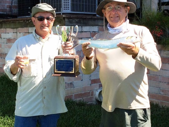 Tom Coon, left, and John McHugh  hold up the trophy and the winning fish in the 7th Annual Driftwood Landing Ladyfish Tournament.
