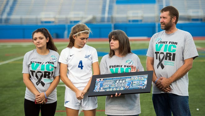 Elizabeth Swiger, from left, stands with her sister, Catherine, mom, Dianne and father, Dana, after being present a photo collage of Tori Swiger, prior to the start of Spring Grove's Melanoma Night, Wednesday, September 27, 2017. Spring Grove held it's third annual Melanoma Night, remembering Tori Swiger, who died July 22 from malignant melanoma and was a 2016 graduate of Spring Grove. The Rockets lost to the Red Land Patriots, 2-1, in double overtime.