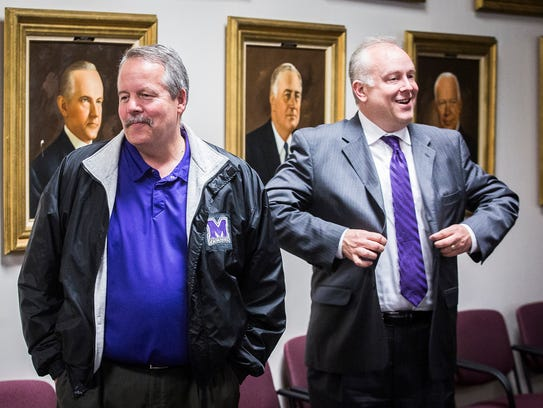 Athletic director Tom Lyon speaks with superintendent