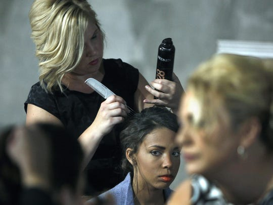 Hair stylist and makeup artist Rebekka Kirchgessner, left, of Irondequoit prepares the hair of model Katie Furfaro in this file photo. Hair stylists will be allowed to return to work under phase two of New York's coronavirus reopening process.