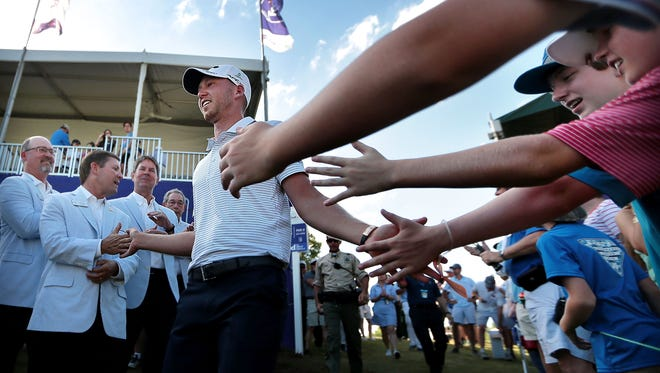 Daniel Berger is congratulated by fans as he returns to the 18th green for his trophy after the final round of the FedEx St. Jude Classic Golf Tournament at Southwind Sunday. Berger finished at 10-under par to win the tournament for the second year in a row.